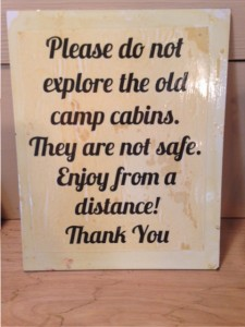 "Nimrod Hall Writers' Workshop sign reading, ""Please do not explore the old camp cabins. They are not safe. Enjoy from a distance! Thank you"""