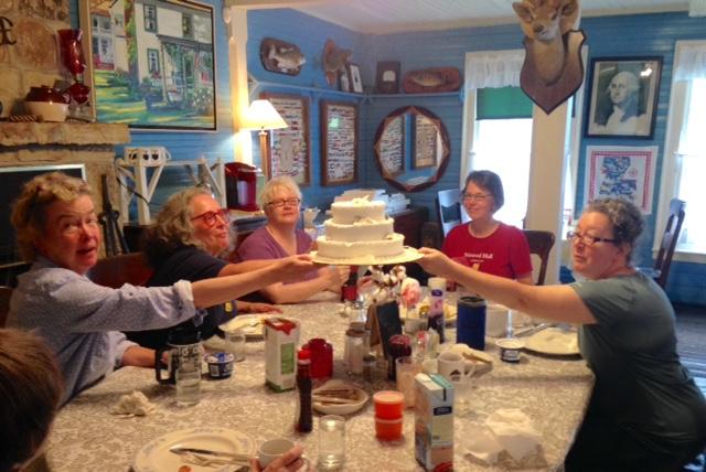 Nimrod Hall writers lifting fake wedding cake at breakfast table