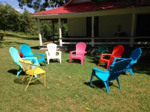 brightly painted chairs on lawn at Nimrod Hall Writers' Workshop