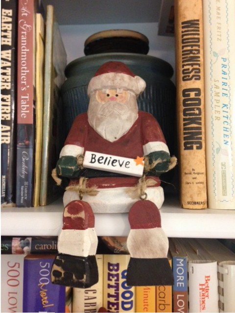 "Santa Claus figurine holding ""Believe"" sign"