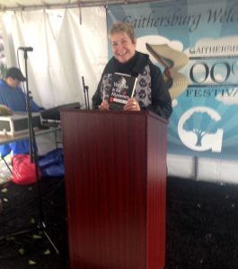 Vivian Lawry speaking at Gaithersburg Book Festival, holding copy of Virginia is for Mysteries
