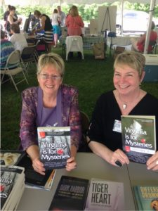 Linda Thornburg and Vivian Lawry holding copies of Virginia is for Mysteries at Radford Reads festival