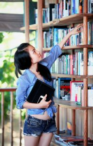 book addict reaching shelf
