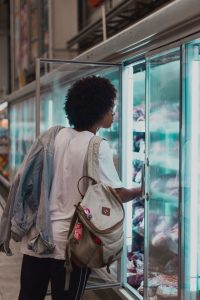 shopper in frozen food or cold storage section of grocery